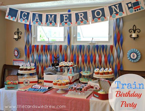 red and blue train themed choo choo first birthday party dessert table with train letter banner sign and crepe paper twisted backdrop