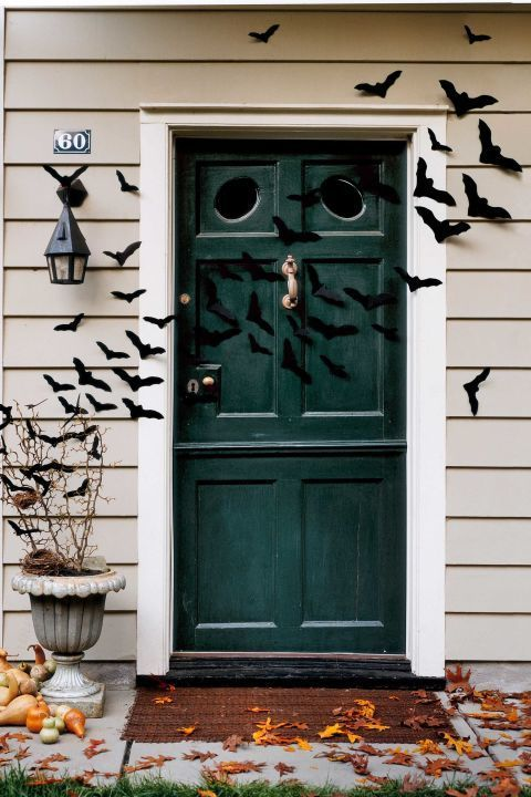 Why stop at the front door? Extend a cloud of bats across the porch and into the entryway for an even bigger statement. Click through for the tutorial and more Halloween door decorations.