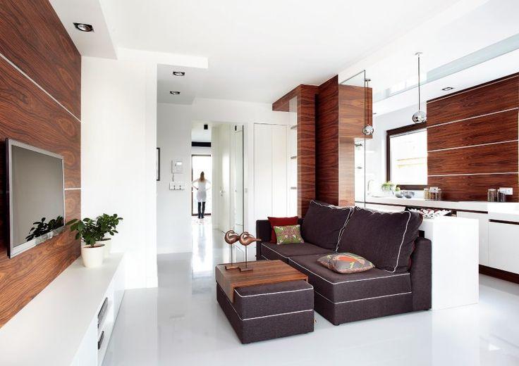 Nowoczesny salon został dobrze zaprojektowany, a w doborze kolorów i materiałów nie było przypadku. Aranżacja salonu z kuchnią miała być jasna, przestronna i funkcjonalna. Białe podłogi z żywicy świetnie rozświetlają wnętrza w towarzystwie drewna. W takim salonie poczujesz się komfortowo.