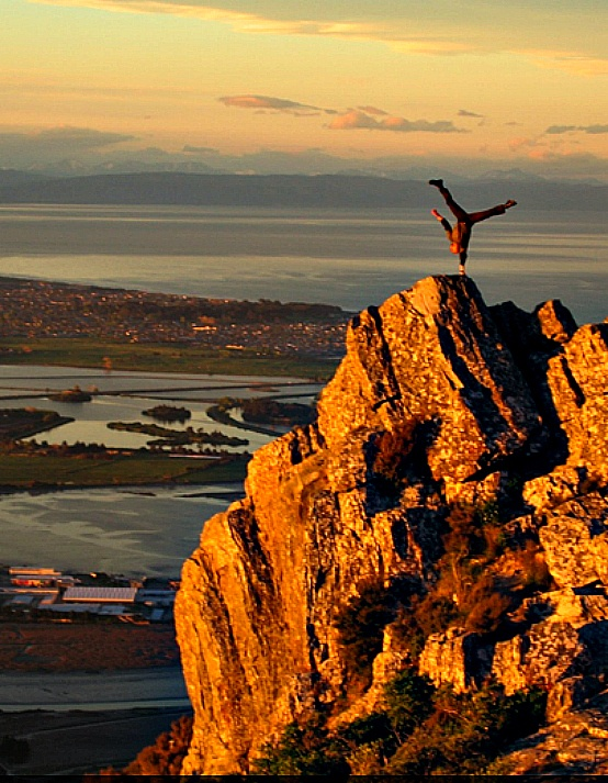 One-handed hand stand on Castle Rock above Christchurch, New Zealand beautiful! Loved and Pinned by www.downdogboutique.com to our Yoga community boards