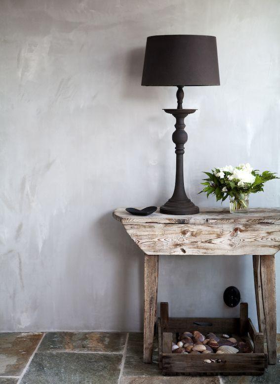 Det vackert flammiga och matta väggarna gjordes av en blandning av spackel och murbruk. Bordet är ett gammalt loppisfynd som stått i ett växthus. Trätråg med snäckor samlade från resor. Svart lampa från PB home. via Skona Hem