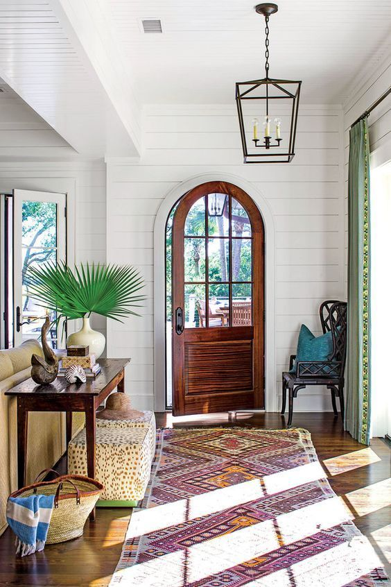 Island-style infused entryway with an iron pendant lantern, palm frond arrangement and vintage Indian runner rug.