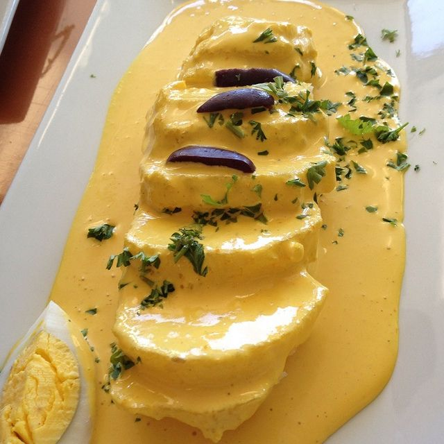 Papas a la Huancaina - Peruvian. Potatoes in a spicy cheese sauce served with egg, olives, and cilantro garnish.