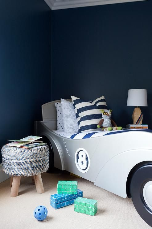 Any little boy would be happy to sleep in this beautifully designed navy blue bedroom equipped with a stunning silver race car bed dressed in blue and white awning striped bedding accented with a blue stars sheet set.