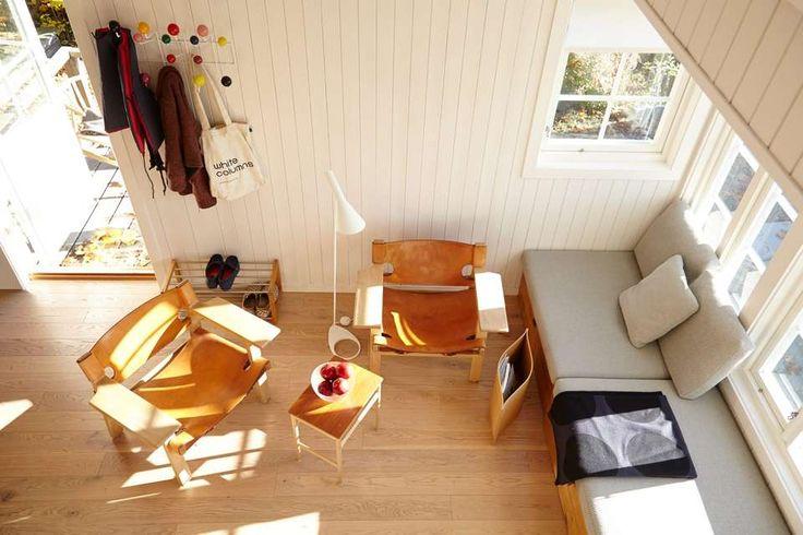 Hytte 82, Bleikøya, Oslo. KUBIKK FREMFOR KVADRATMETER: Hems i stedet for to etasjer gjør det lille allrommet åpent og luftig. Et praktisk sett med småbord fungerer godt i et lite rom. Hemsen har en komfortabel plass til 4 stykker. Lenestol av Wegner.
