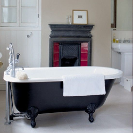 Victorian Bathroom. Roll top bath with an original cast iron fireplace.