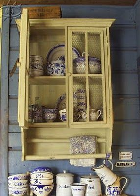 Charming... Old yellow cupboard has a chicken wire front and comes complete with towel bars.