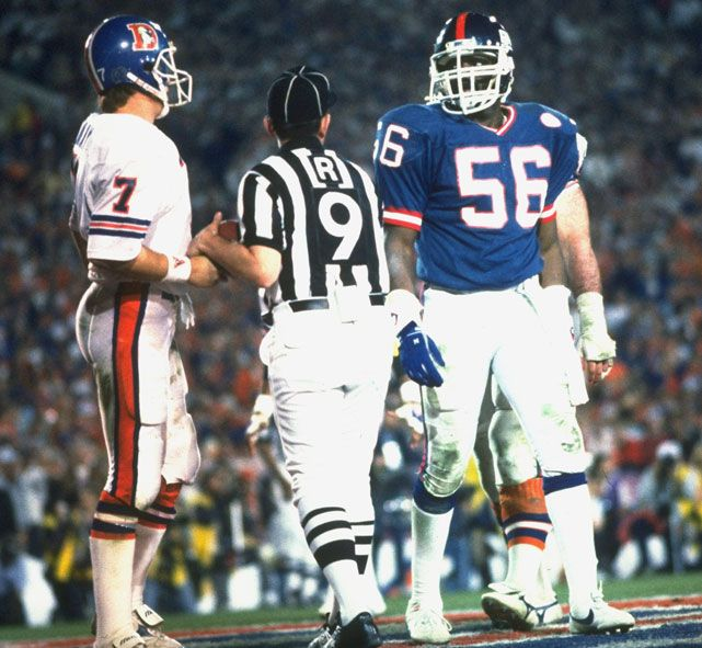 Lawrence Taylor stares down John Elway during the second quarter of Super Bowl XXI. The Broncos QB threw for 304 yards and a touchdown but the Giants prevailed, 39-20.  GALLERY: Super Bowl Covers | Rare John Elway Photos| Classic Sports Posters