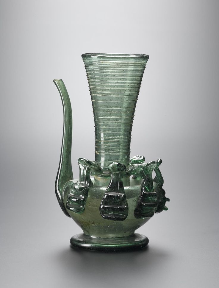 Ewer of light green glass with a squat globular body resting on a low splayed foot, a tall cylindrical neck flaring towards a wide circular mouth and decorated with fine spiral lines, a narrow spout with a broken tip, six applied handles attached around the body and attached to the base of the neck: probably Middle East, Iran, 19th century.