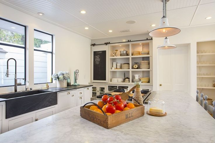 Little details make a world of difference in this cozy kitchen. A barn door-style chalkboard makes it easy to keep track of the grocery list and hide cabinet clutter when necessary. The rustic-chic look is topped off with a wooden tray full of farmers market fresh produce.