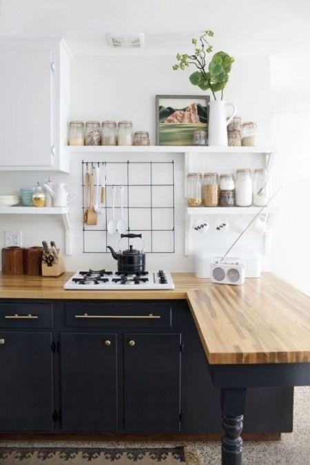 granatowa kuchnia z drewnianym blatem i białymi pólkami ...