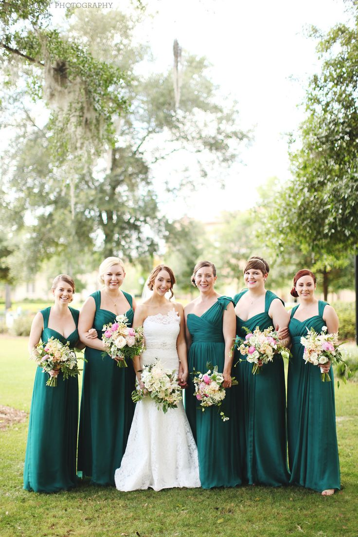 bridesmaid bouquets of light pink peony, peach stock, white scabiosa, white astilbe, snow on the mountain, light pink ranunculus, white majolik spray rose, plumosa, elm, fern & jasmine vine are a standout against emerald green gowns in this spring wedding.