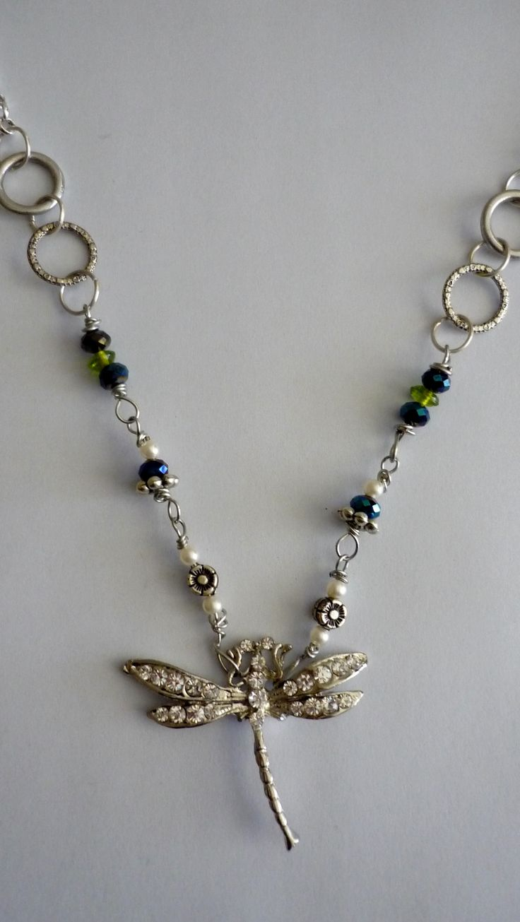 Amanda Harris Diamonti dragonfly on silver chain with silver rings and multiple beads/pearls charms.