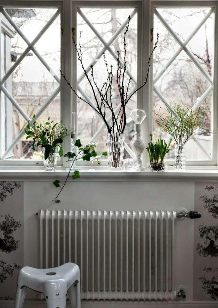 appui de fenetre intérieur décoré de lierre, bouquet de brindilles et feuilles dans des vases en verre