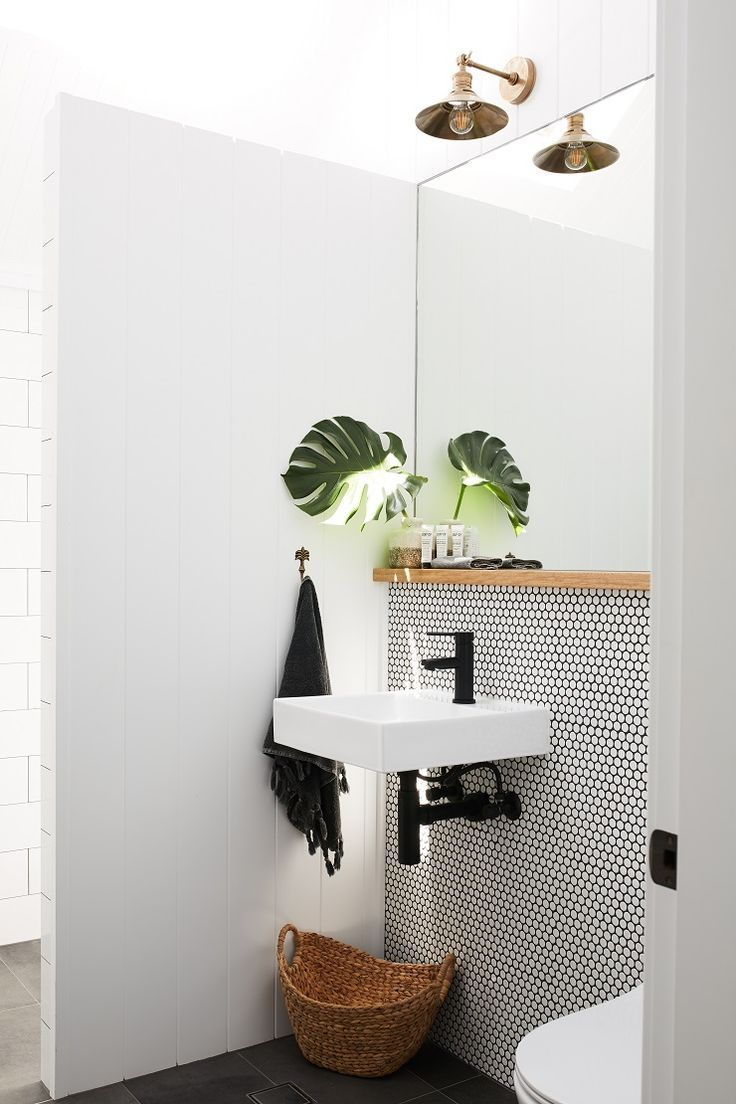 Black mosaic tiles add black fixtures and accessories. Plants in the bathroom