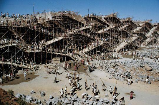 Workers swarm over scaffolding to erect the Nagarjuna Sagar dam in India, May 1963