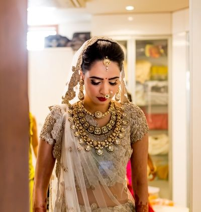 Indian Wedding Jewelry - White and Gold Lehenga with Polki Layered Necklace, Maang Tikka and Nath | WedMeGood #wedmegood #indianjewelry #indianbride #indianwedding #jewelry #necklace #polki