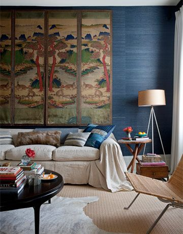 "An Eclectic Living Room - an 18th-century Korean screen hangs above a sofa slipcovered in vintage French linen sheets.  ""It all comes down to contrasts: Mix hard with soft, square with round, blocky with leggy"""
