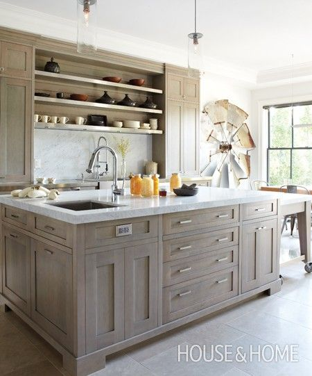 In this kitchen, birch cabinets get a modern finish with grey stain. Honed limestone floors and Carrara marble backsplash and counters add luxury and shine, while homeowner Betsy Aziz's collection of Egyptian pottery layers in an artisanal organic feel. For options to display or conceal, consider adding both open and closed storage.: