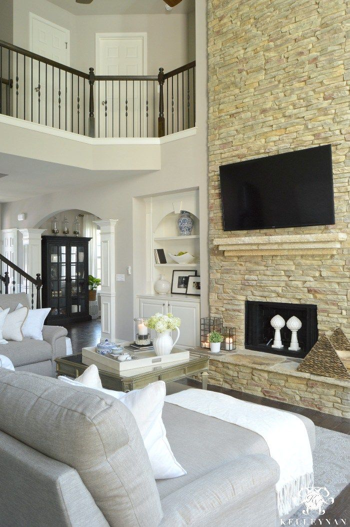 Two Story Great Living Room with Stacked Stone Fireplace and TV Above fireplace