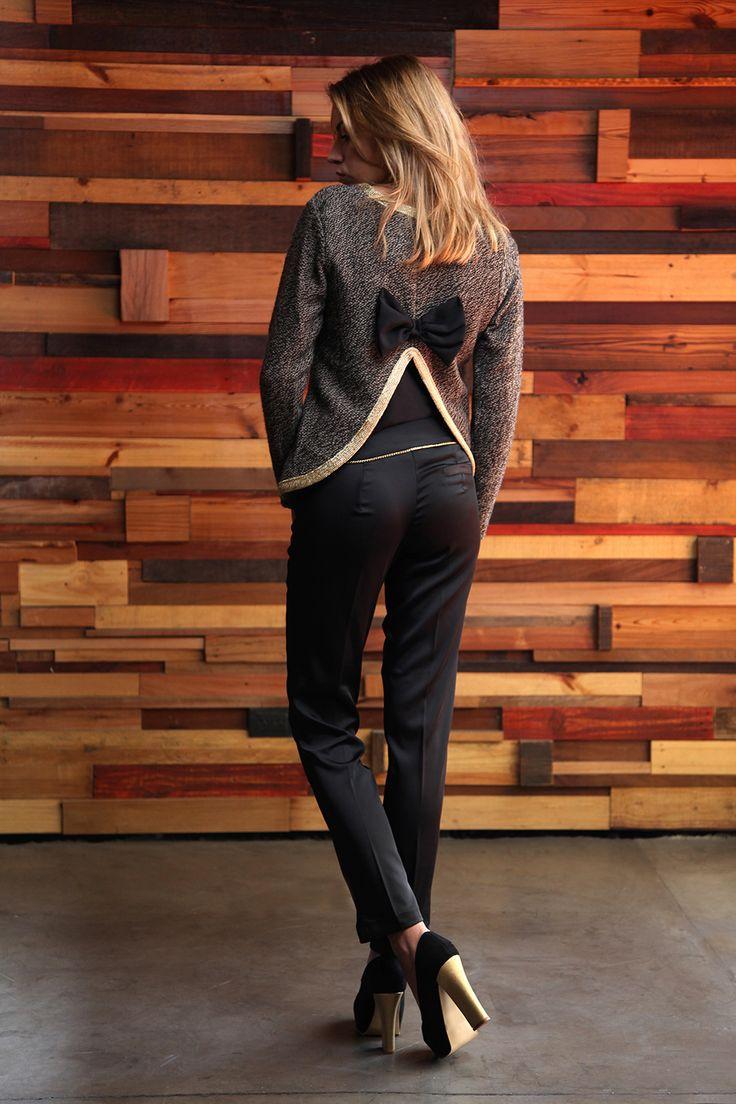 Espalda: Sweater con ribetes en oro y detalle de moño en espalda - Pantalón recto raso de seda con cadena