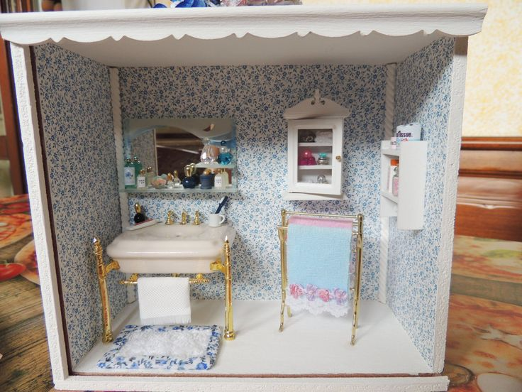 Roombox with bathroom with 1:12, handmade scale miniatures. The roombox was furnished with accessories, including a traditional ceramic sink and mirror glass, decorated metal and entirely handmade, towel rail and wooden cabinets. The walls are covered entirely by hand with wallpaper. Great as a gift or ornament.