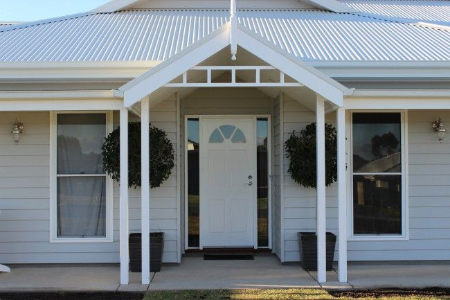 Weatherboard exterior / front door with sidelights / double hung windows - to have plantation shutters installed / grey n white paint / surf mist roof
