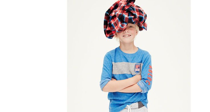 boy in shirt with shirt on his head