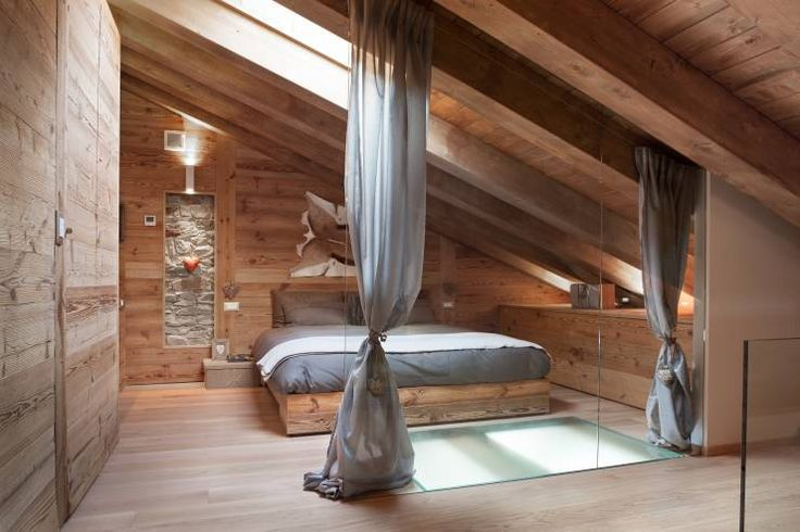 Scandinavian style bedroom with lots of warm wood in the attic by archstudiodesign.