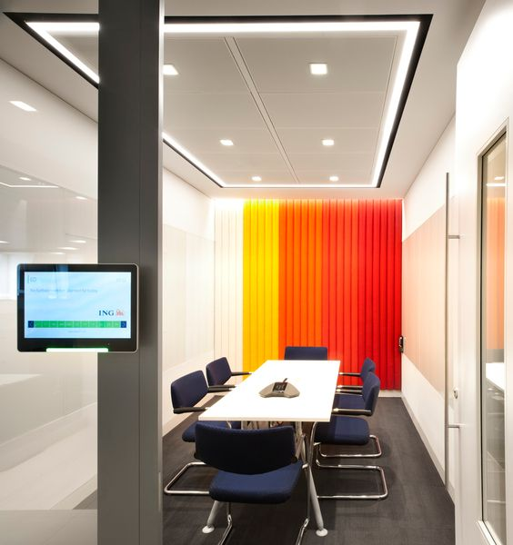 Meeting room with touch screen meeting room booking system interface. The meeting room has a feature wall with a series of red, orange, yellow and white panels, and a rectangle of strip lighting with spot lights to illuminate the space.