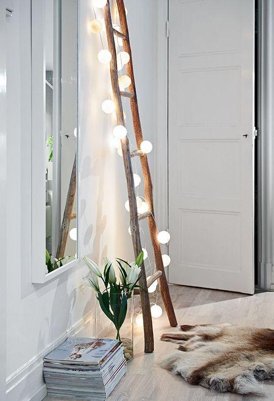 Alegra cualquier rincón poniendo una escalera de madera con una guirnalda de luces apoyada en la pared. Si tienes un espejo cerca el efecto será aún más bonito.