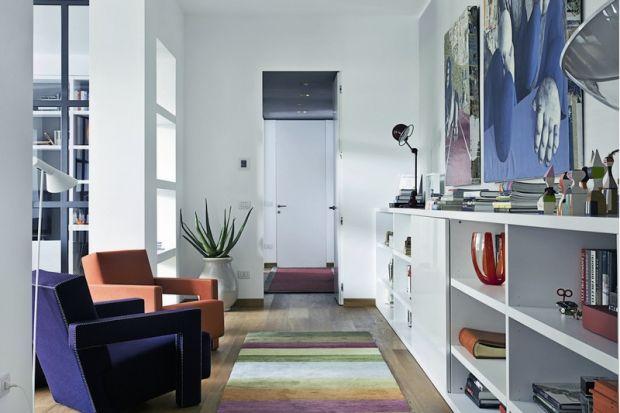 Il living con la tv nascosta dietro il pannello scorrevole della libreria bassa, le poltrone Utrecht di Cassina e il tappeto di Alberto Levi Gallery.