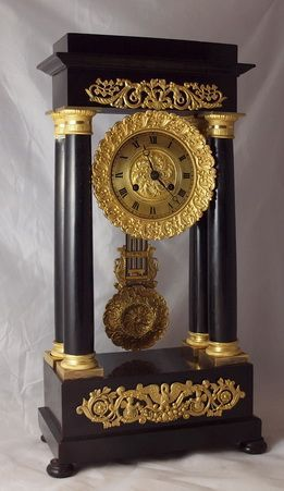 A good quality French portico clock. An ebonised case with ormolu bronze mounts. Well detailed coumn capitals. A gilt bronze dial with decorative bezel and dial centre. A gridiron compensating pendulum. An 8-day duration mechanism striking the 1/2 hours and hours on a bell. Circa 1840.