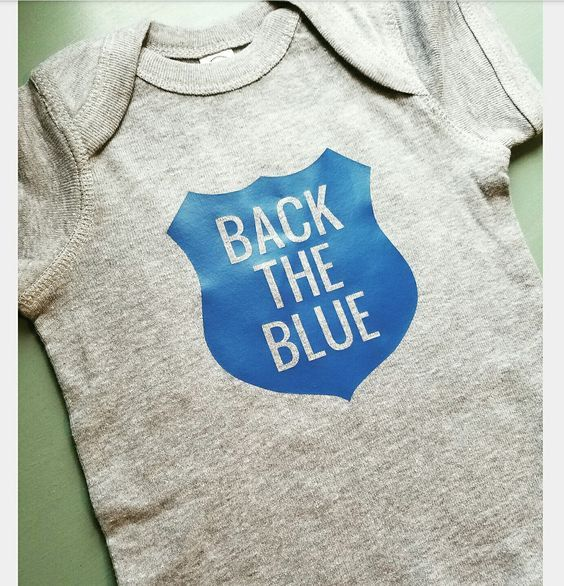 Back the Blue printed on a Rabbit Skins brand baby onesie. Features lap-shoulders and 3 snaps at the bottom. Sizing help is located in product photos. Sizes available include Newborn, 6 month, 12 mont