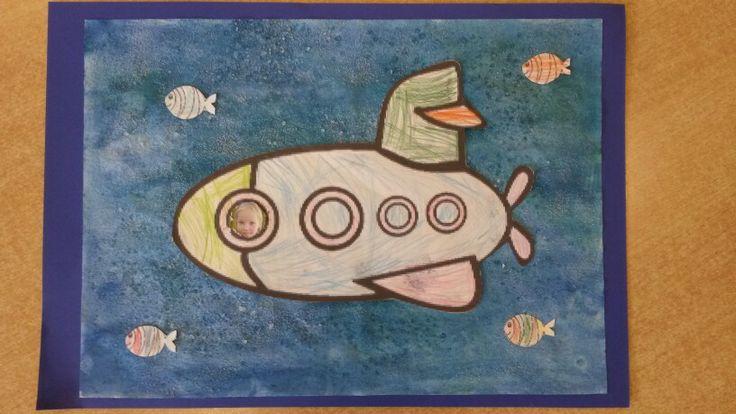 Submarine / Onderzeeër - achtergrond van 3 kleuren blauwe waterverf, papier goed nat maken, hierna zeezout en tafelzout eroverheen. Wanneer papier droog is zout eraf vegen. Onderzeeër en visjes kleuren. Eerste rondje van de onderzeeër uitprikken, vliegerpapier erachter met daarop foto van het kind.