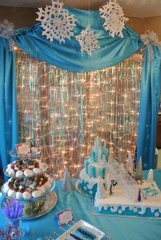 Frozen backdrop  Whited netted Christmas lights, sheer fabric, 2 iridescent door fringe curtains, Aqua satin drapery, and 3-D hanging snowflakes