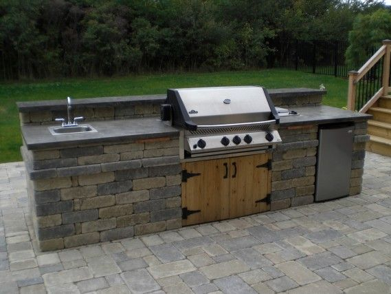 An outdoor kitchen with Napoleon grill, sink, and fridge allow and bar top seating. By Signature Outdoor Concepts