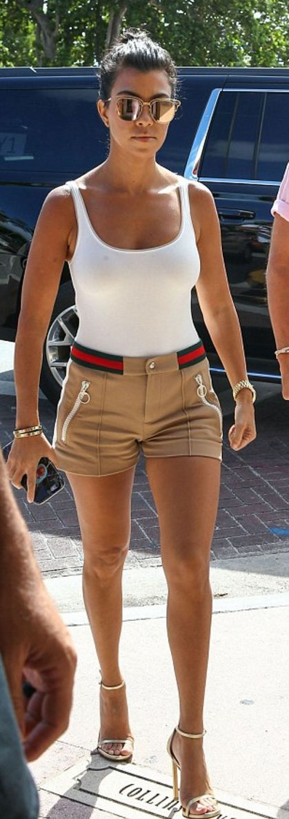 Kourtney Kardashian: Shirt -Wolford  Shorts – Gucci  Bracelet – Cartier  Shoes – Stuart Weitzman  Sunglasses – Dior