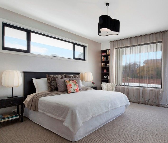 Hampton master bedroom with feature pendant lighting and carpeted floor.