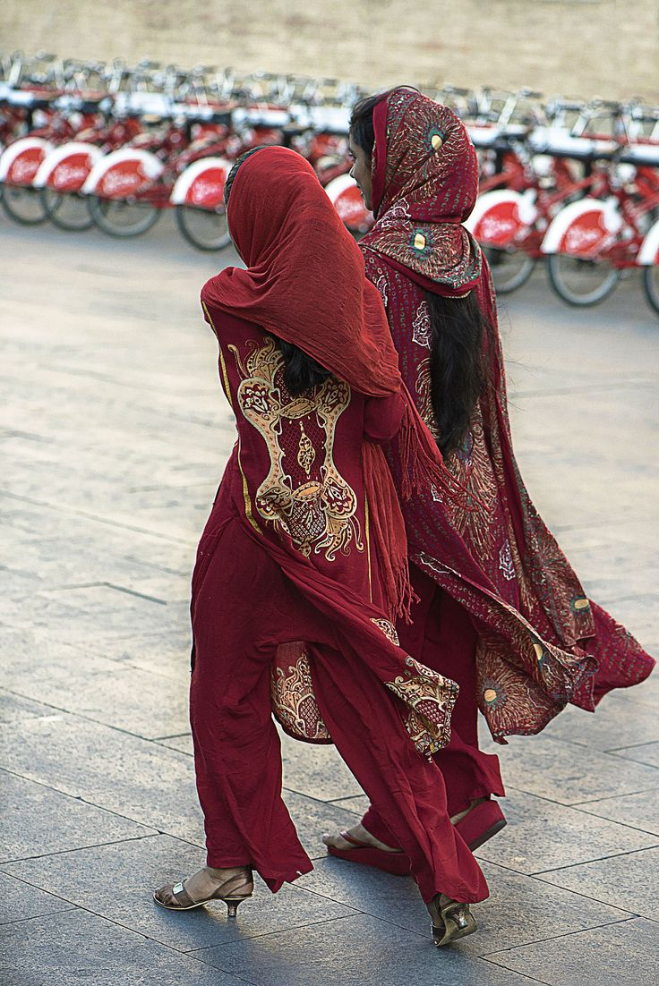 Women decked out in red walk past a bike stand
