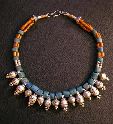 Blue sandcast and amber-colored glass beads from Nigeria highlight the interspersed breast beads from Ethiopia. A simple but eye-catching necklace with a sterling silver clasp.