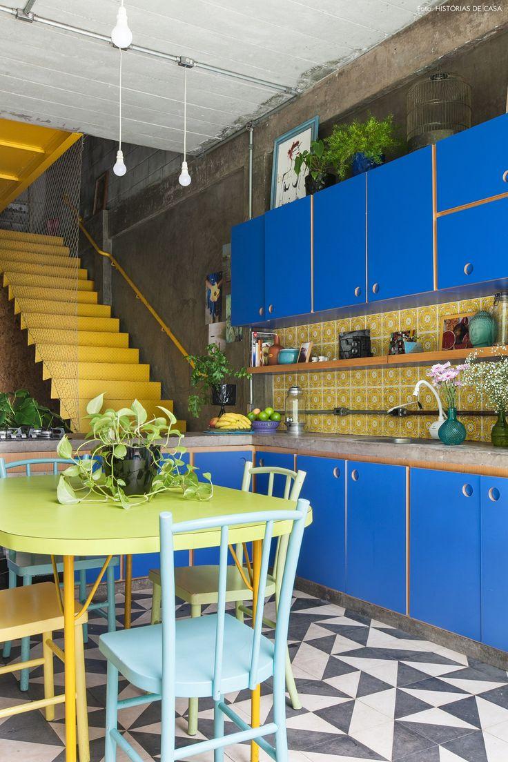 Cozinha colorida com parede de cimento queimado, armários na cor azul, azulejos estampados em amarelo e piso de ladrilho hidráulico.