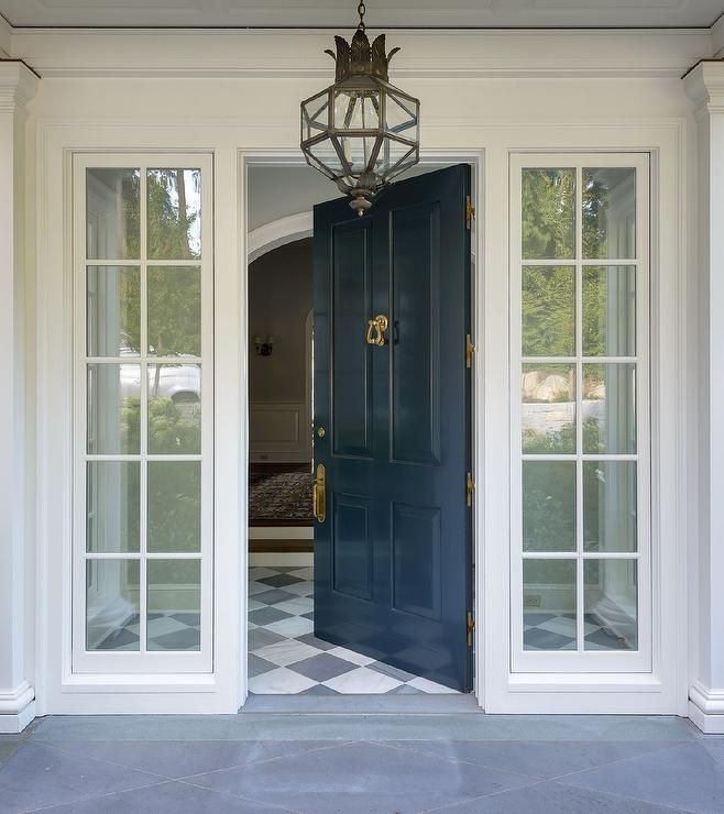 dark blue gloss front door with a white house and interesting lantern