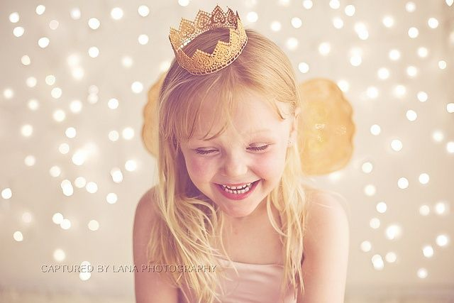 child in crown photography with christmas light bokeh by Captured By Lana