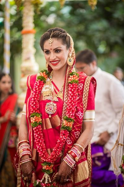 South Indian Bride - Bride in a Red and Gold Kanjivaram Saree with a Red and Orange Floral Garland | WedMeGood #wedmegood #indianbride #southindianbride #southindianoutfit #kaanjivara #red #gold