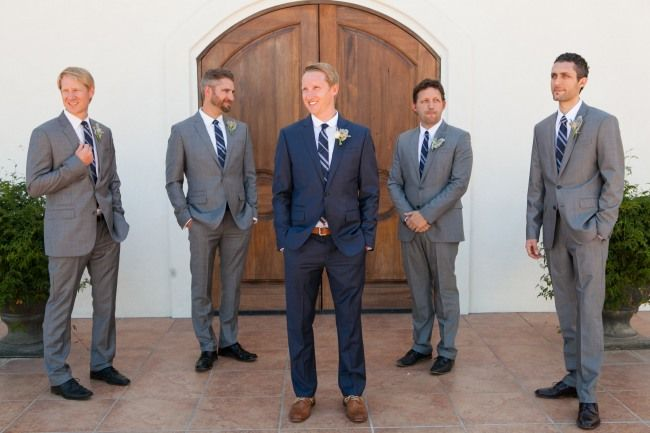 Groom in blue with shoes and grey tie, groomsmen in gray with shoes and navy tie