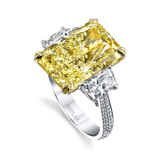 Just as a couple meets at the ceremony, two rows of pave diamonds march down the band to come together as one with a three-stone setting representing past, present and future with a radiant cut diamond in yellow gold nestled between two smaller stones set in platinum in this magnificent Harry Kotlar ring.