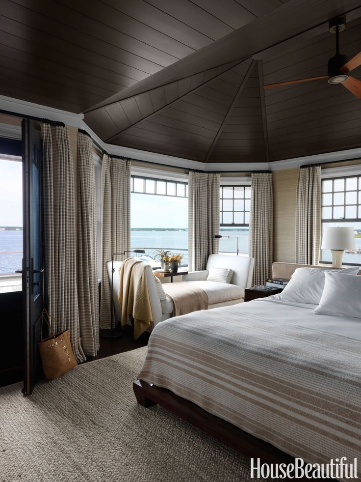"""In a Shingle Style beach house in Long Island, New York, walls in the master bedroom are covered in Donghia's Silk Texture II, and the ceiling is painted in Benjamin Moore Regal Select in Night Horizon to dramatize the soaring space. The horizontal stripes on the curtains, Hines & Company's Malabar, """"mimic the horizon line,"""" designer Rob Southern explains. Custom chaise in Great Plains' Weathered by Holly Hunt. Bed linens, Schweitzer Linen.   - HarpersBAZAAR.com"""