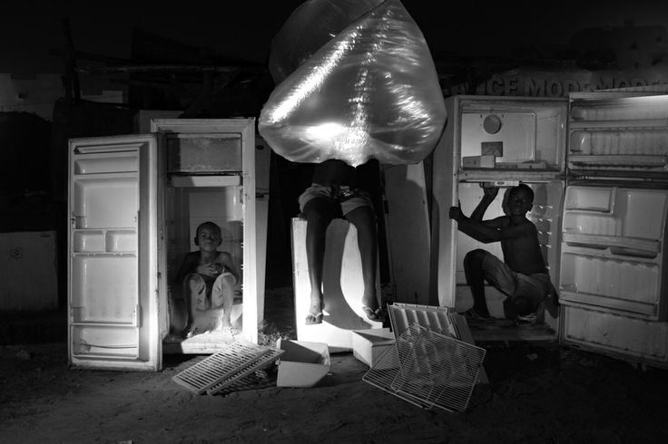 Notre monde est-il durable? (Is our world sustainable?), Bakary Emmanuel Daou  (b. 1960, Mali), 2010, Chromira print on archival paper. Working w/dramatic shadows, Daou creates seductive, allegorical images. Here, he has photographed 3 children crouching w/in refrigerators that do not work, while a luminous plastic bag of water floats in the foreground. For Daou, refrigerators & plastic bags symbolize longevity- these things endure. Humans & water, by contrast, are fragile. #earthmatters…