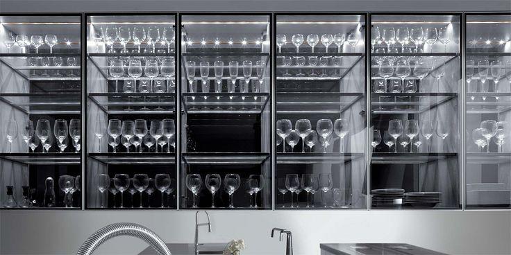 Nei pensili della cucina, un'architettura rigorosa e dal forte impatto grafico, costituita da ripiani in vetro poggiati su un telaio in acciaio.